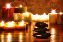 Symbolic Zen Stones Cairn and Meditation Candles. Symbolic Zen black polished smooth stones cairn stack and candles soft glowing in a spiritual religious temple royalty free stock image