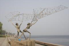 Symbolical postacie rybacy rzuca sieć na banku jezioro zdjęcie royalty free