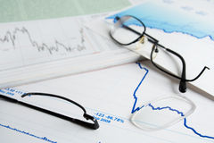 Symbolics of financial crisis. Broken glasses and tendency to reduction of quotations Royalty Free Stock Photo