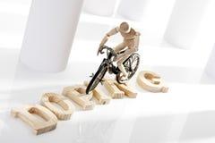 Symbolisch für das Lackieren: Hölzerne Figürchen auf Rennrad Lizenzfreies Stockfoto