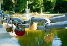 Symbolische liefdehangsloten vast aan het traliewerk van een brug royalty-vrije stock afbeelding