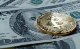 Symbolische Münzen von bitcoin auf Banknoten von hundert Dollar Lizenzfreies Stockbild