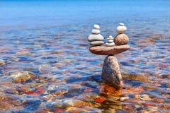 Symbolische Skalen von stehenden Steinen im Wasser Das Konzept von Stockbilder