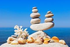 Symbolische Skalen von weißen Steinen, von Oberteilen und von Koralle auf einem Hintergrund des Sommermeeres und des blauen Himme Lizenzfreies Stockbild