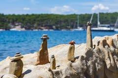 Symbolische Steinfigürchen auf der felsigen Küste stockbilder