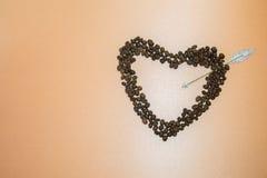Symbolisches Herz von den Kaffeebohnen durchbohrt durch einen Pfeil auf heller Braue Stockbild