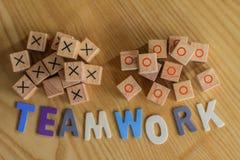 Symbolisera teamwork med träkvarter och färgade bokstäver med arkivfoto
