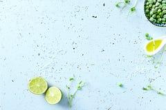 Symbolisk matbakgrund med limefrukt, ärtagroddar, salta och djupfrysta ärtor för hav royaltyfri foto