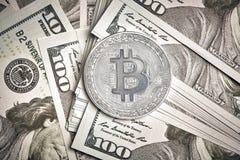 Symboliska mynt av bitcoin på sedlar av hundra dollar Utbytesbitcoinkassa för en dollar Arkivfoto