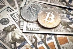 Symboliska mynt av bitcoin på sedlar av hundra dollar Utbytesbitcoinkassa för en dollar Royaltyfri Foto