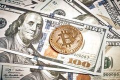 Symboliska mynt av bitcoin på sedlar av hundra dollar Utbytesbitcoinkassa för en dollar Royaltyfri Bild