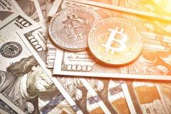 Symboliska mynt av bitcoin på sedlar av hundra dollar Utbytesbitcoinkassa för en dollar Solsignalljus Arkivfoto