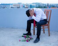 A disheartened man in a suit, broken-hearted after being rejected. Symbolism of being rejected. Man trashing the flowers he wanted to give as a gift Stock Photos