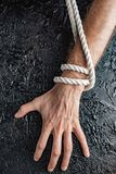 Male hands are pulling the rope on a black background. Symbolism containment of man`s connection by means of bound hands with a rope stock photo