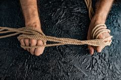 Male hands are pulling the rope on a black background. Symbolism containment of man`s connection by means of bound hands with a rope royalty free stock photo