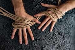Male hands are pulling the rope on a black background. Symbolism containment of man`s connection by means of bound hands with a rope stock images