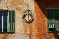Symbolism time: vintage watch on a shabby wall. Symbolism, temporary changes: vintage watch on dilapidated building in the Sospel village medieval French royalty free stock photo