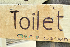 Symbolize toilets on wood background Royalty Free Stock Photos