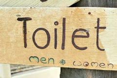 Symbolize toilets on wood background Royalty Free Stock Photos