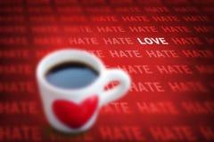 Symbolkoppen för svart kaffe och hjärtamed ord hatar och älskar arkivfoton