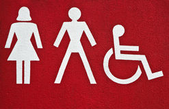 Symbols on building with sanitary. Symbols female, male and physically disabled on building with sanitary rooms Royalty Free Stock Photo