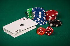 Symbols in the casino games. Deck of cards with an ace and a joker on top, chips and dice on a green table Stock Photo