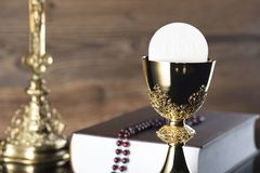 Catholic religion theme - Holy communion concept. Symbols of Christianity religion, brown wooden background. Place for text Royalty Free Stock Image