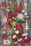 Symbols of Christmas and Joy Sign Decoration. Symbols of christmas with bauble decorations and gold glitter joy sign on distressed wood background Royalty Free Stock Photo