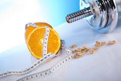 Symbols of diet. Dumbells with corn flakes with orange and measuring tape Royalty Free Stock Photography