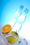 Symbols of diet. Bottles of mineral water with fruits with measuring tape Royalty Free Stock Photos