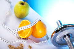 Symbols of diet. Dumbells and fruits with measuring tape Royalty Free Stock Images