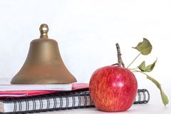 Symbols for education, red delicious homegrown apple, brass school bell stacked on black spiral bound sketch notebook, red folder royalty free stock photos