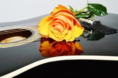 Symbols of expectation. The rose next to the strings of the guitar, beautifully creating the reflection on the surface of the instrument, symbols of love Stock Photo