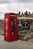 Symbols of Great Britain. Symbols associated with Great Britain - red telephone booth, fish and chips directional sign, old castle, grey skies Royalty Free Stock Image