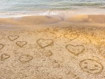 Symbols of the hearts and round face drawing on the sand on the beach of Tel Baruch . Tel Aviv Promenade. Israel. Close up image stock images