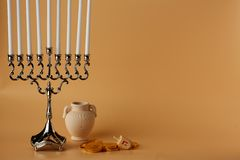 Image of jewish holiday Hanukkah with menorah and wooden dreidel, jug, coins stock photography