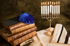 Symbols of judaism. Bible, prayer shawl, jewish cap and nine candle menorah Stock Photo
