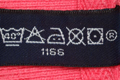 Symbols on label clothes. Close up. Symbols on label clothes showing as it is necessary to look after these clothes. Close up stock photo