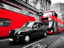 Symbols of London, the UK. Red buses, black taxi cab. Black and white. Symbols of London, the UK. Red buses and black taxi cab in motion. Black and white with stock images