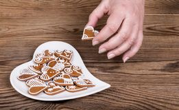Female hand holding a beautiful sweet heart for good luck and white plate. Symbols of love, bond, marriage or friendship on a brown wood background stock photography