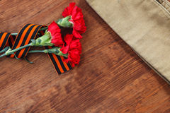 Symbols of Victory in Great Patriotic War three red flower and Soldier's forage cap on a table.  selective focus image Royalty Free Stock Images