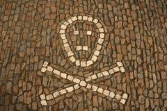 Symbool van gekruiste die beenderen en schedel van witte cobbles ter plaatse worden gecreeerd Stock Foto