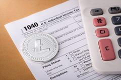 Symbool van het Litecoin het fysieke zilveren muntstuk op 1040 belastingsvorm met calculator Royalty-vrije Stock Fotografie