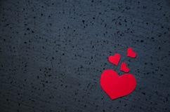 Symbool van liefde en van de valentijnskaartendag achtergrond - heldere rode harten op een zwarte achtergrond Het concept van de  Stock Foto's