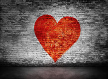 Symbool van liefde op duistere bakstenen muur wordt geschilderd die stock fotografie