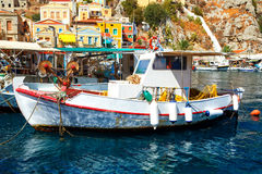 Symi island - Colorful houses and small boats at heart of village Stock Photos