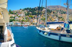 SYMI ISLAND, GREECE, JUNE 25, 2013: View on beautiful classic sea ocean yachts, Greek sea port, houses on island hills, tourists, royalty free stock image