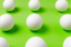 Symmetri av vita ägg på ljust ljus - grön bakgrund Arkivfoto