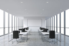 A symmetric corporate workplaces equipped by modern laptops in a modern panoramic office, white copy space in the windows.. Black leather chairs and white Stock Images