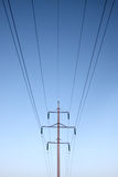 Symmetric electrical lines on mast. Symmetric electrical lines mast cables blue sky Stock Images